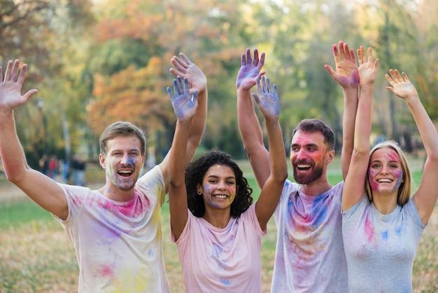Amigos posando mientras sostiene las manos de colores en el aire