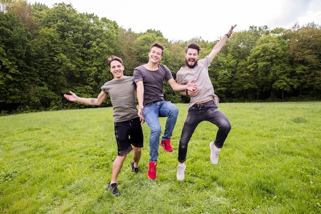 Amigos positivos saltando en el prado