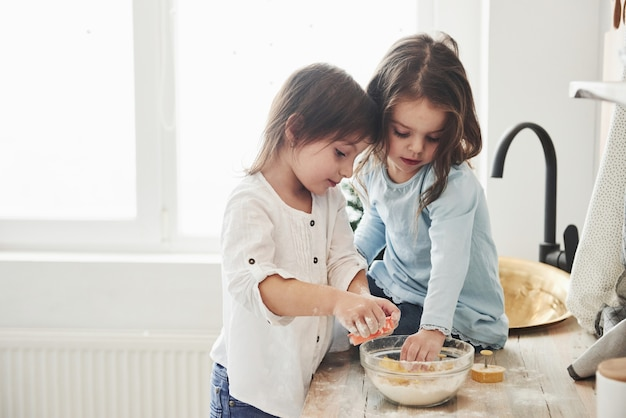 Amigos preescolares que aprenden a cocinar con harina en la cocina blanca