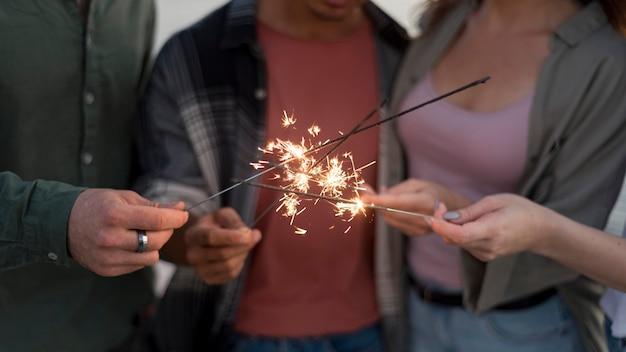 Amigos de primer plano con fuegos artificiales brillantes