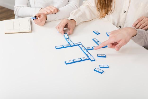 Amigos de primer plano jugando un juego de dominó