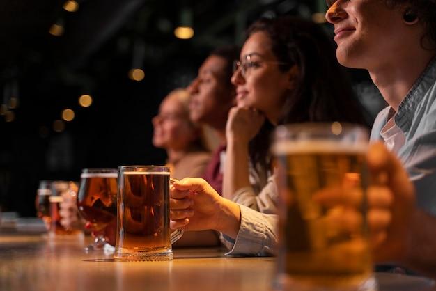 Amigos de primer plano sosteniendo jarras de cerveza