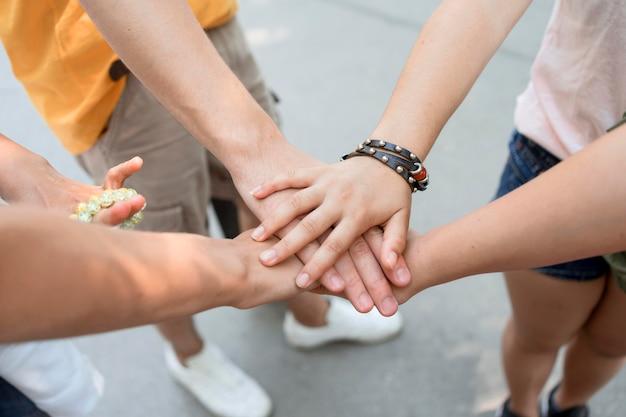 Amigos de primer plano tocando las manos