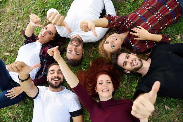 Amigos con los pulgares arriba tumbados en el césped de un parque