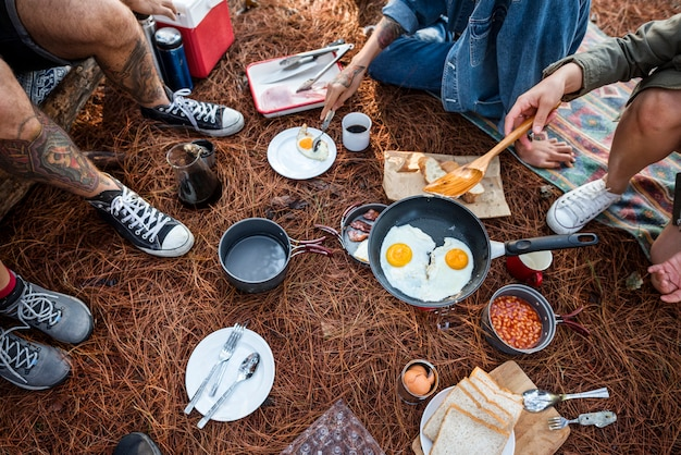 Amigos que acampan comiendo concepto de comida