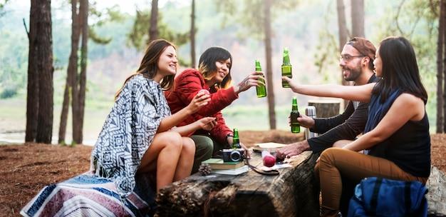 Amigos que acampan teniendo concepto de las bebidas