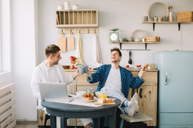 Amigos que animan la taza de café que se sienta con la comida fresca y el ordenador portátil en la tabla