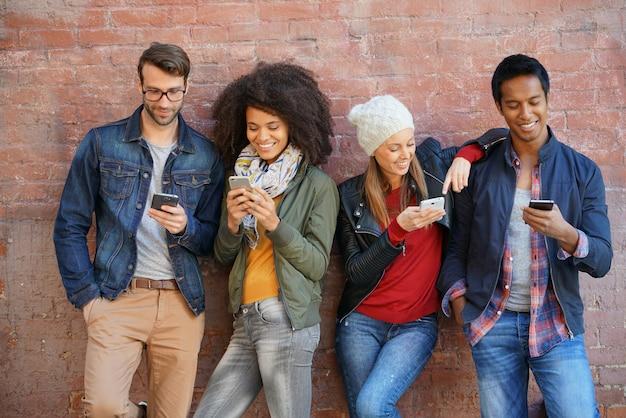 Amigos que se apoyan en la pared de ladrillo, jugando con teléfonos inteligentes