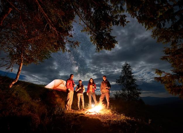 Amigos que descansan junto a la fogata y la carpa naranja en la noche cerca del bosque bajo el cielo nublado contra las siluetas de las montañas en la distancia. ellos sostienen cerveza