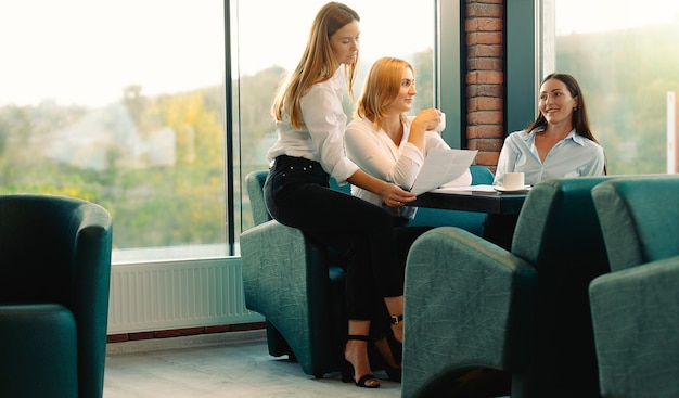 Amigos que se divierten tomando café en la lluvia de ideas de la oficina moderna bajo un nuevo proyecto. las mujeres jóvenes discuten sentarse juntas a la mesa y pasar tiempo en la pausa para el café.