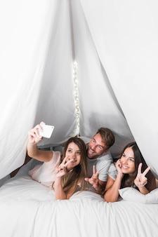 Amigos que mienten en la cama que toma el selfie del teléfono móvil que muestra el signo de la paz