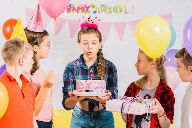 Amigos que miran a la muchacha con la torta de cumpleaños que sopla la vela