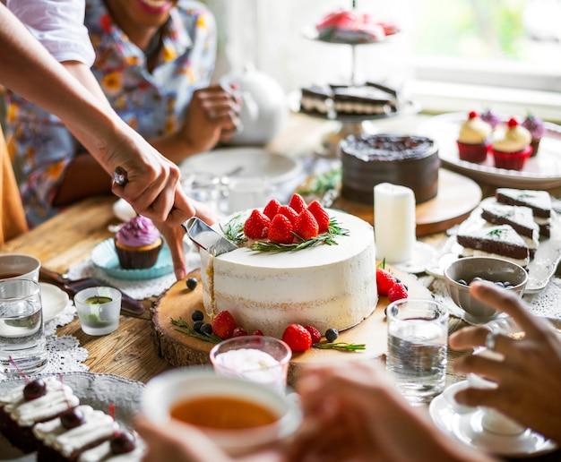 Amigos que se reúnen en la fiesta del té comer tortas disfrutar la felicidad