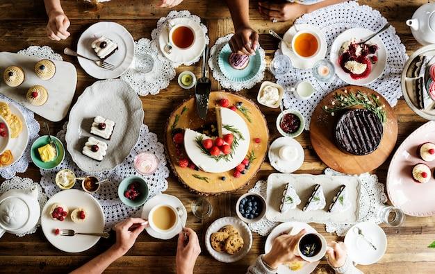 Amigos que se reúnen en la fiesta del té comiendo tortas disfrute la felicidad