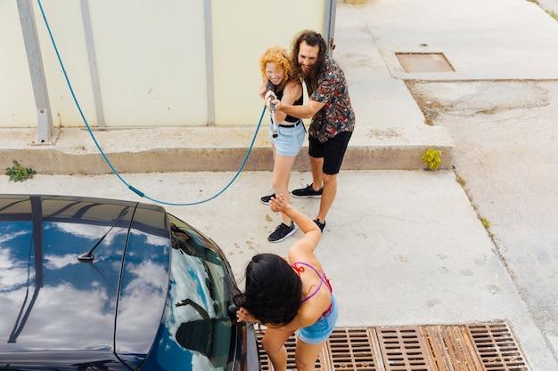 Amigos que salpican el agua en la mujer que está parada cerca del coche