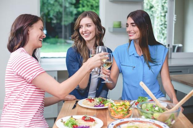 Amigos que tuestan una copa de vino mientras comen