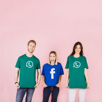 Amigos que usan la camiseta del icono de los medios sociales en el contexto rosado