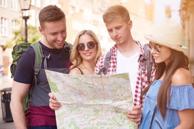 Amigos que usan el mapa mientras hacen turismo