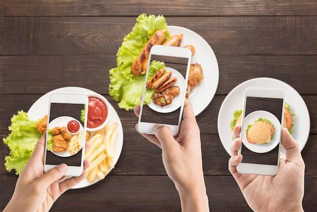 Amigos que usan teléfonos inteligentes para tomar fotos de salchichas, chuletas de cerdo, papas fritas, pollo y hamburguesas