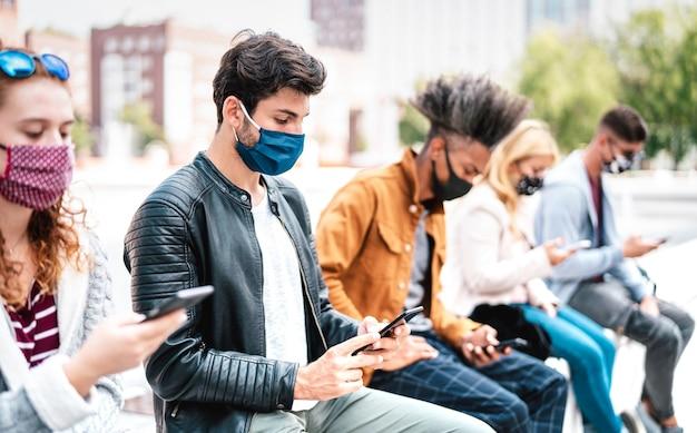 Amigos que usan teléfonos móviles cubiertos por una mascarilla en la segunda ola de covid: enfoque en el primer tipo izquierdo