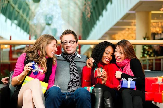 Amigos con regalos de navidad y bolsas en el centro comercial