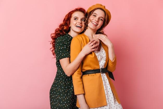 Amigos relajados abrazándose sobre fondo rosa. foto de estudio de dos chicas lindas mirando a la cámara.