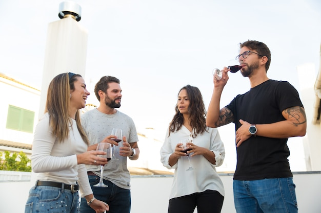 Amigos relajados bebiendo vino y discutiendo noticias