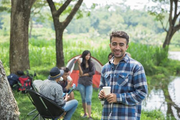 Amigos relajantes carpas exteriores en camping