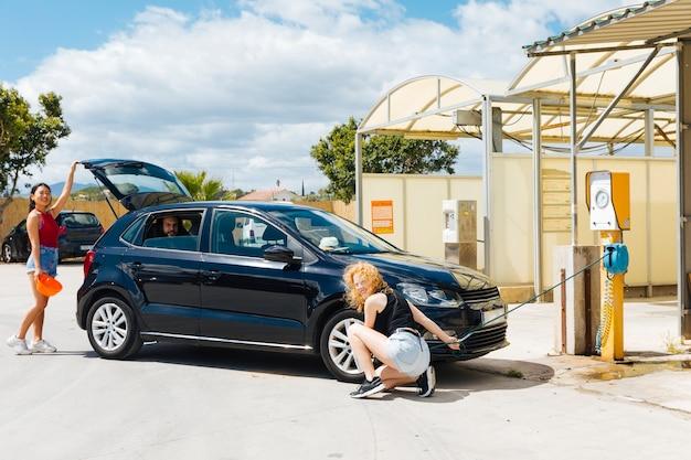 Amigos reparando el coche mientras se detienen en la estación de servicio