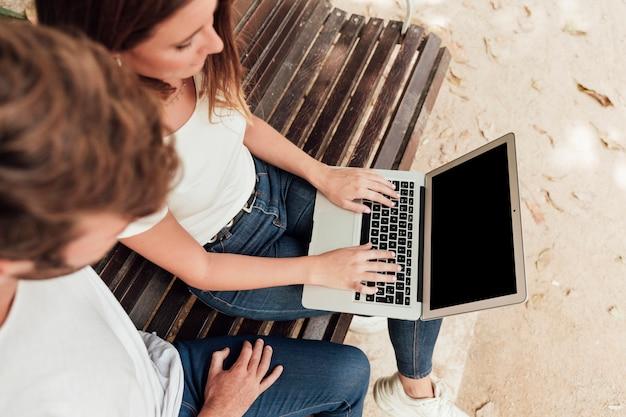 Amigos revisando la computadora portátil en un banco
