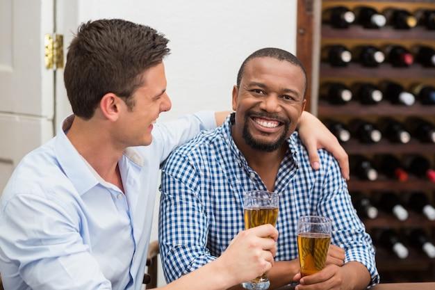 Amigos riendo mientras tomando cerveza