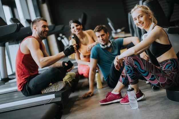 Amigos en ropa deportiva hablando juntos mientras están de pie en un gimnasio después de un entrenamiento