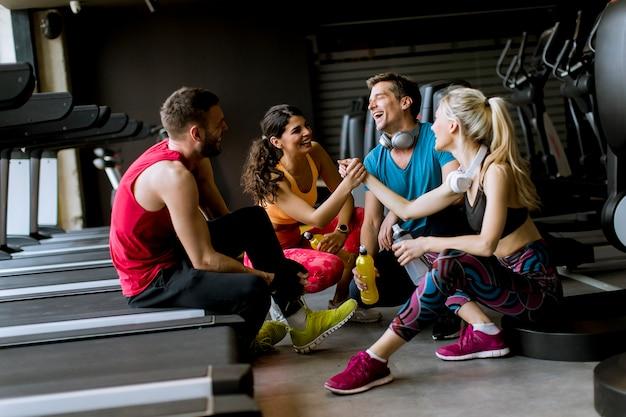 Amigos en ropa deportiva hablando y riendo juntos mientras descansan en el gimnasio después de un entrenamiento