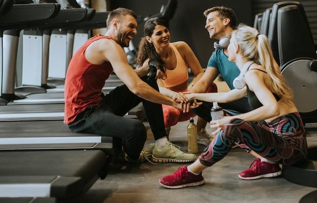 Amigos en ropa deportiva hablando y riendo juntos mientras están sentados en el piso de un gimnasio después de un entrenamiento