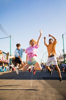 Amigos saltando en las calles del parque de atracciones