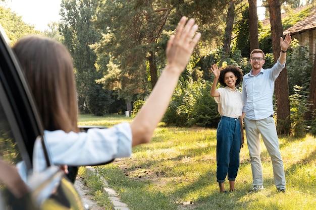 Amigos saludando el uno al otro al aire libre desde el coche