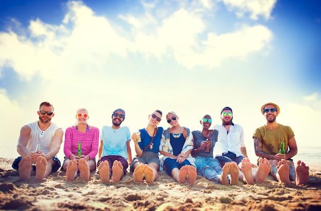 Amigos sentados en la arena en una playa