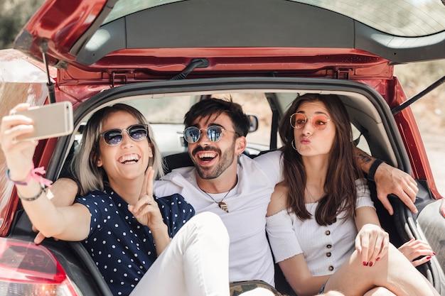 Amigos sentados en el baúl del auto tomando selfie a través del teléfono inteligente