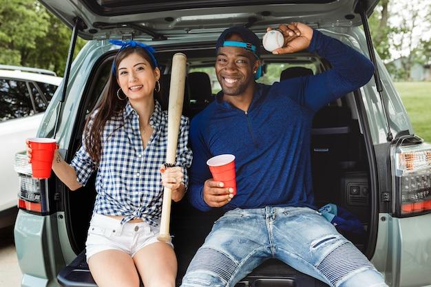 Amigos sentados y bebiendo en el maletero del coche en una fiesta en el portón trasero