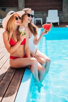 Amigos sentados en el borde de la piscina