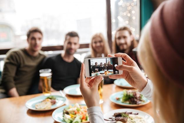Amigos sentados en la cafetería y beber alcohol y hacer photo