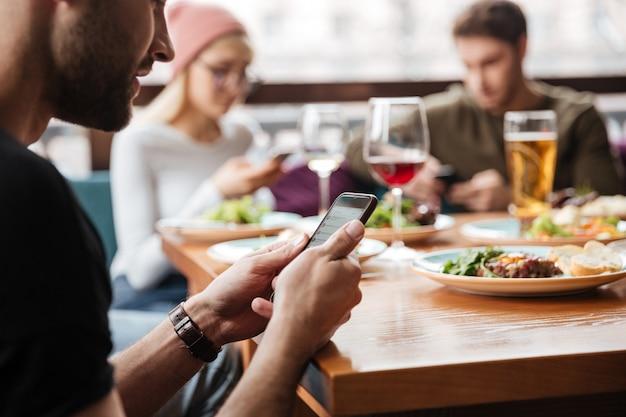 Amigos sentados en la cafetería y usando teléfonos móviles