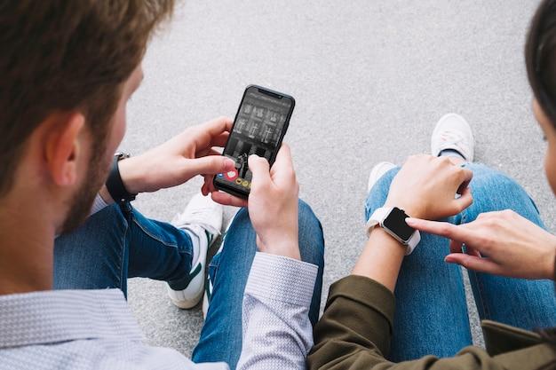 Amigos sentados en la calle conectando reloj inteligente con teléfono móvil