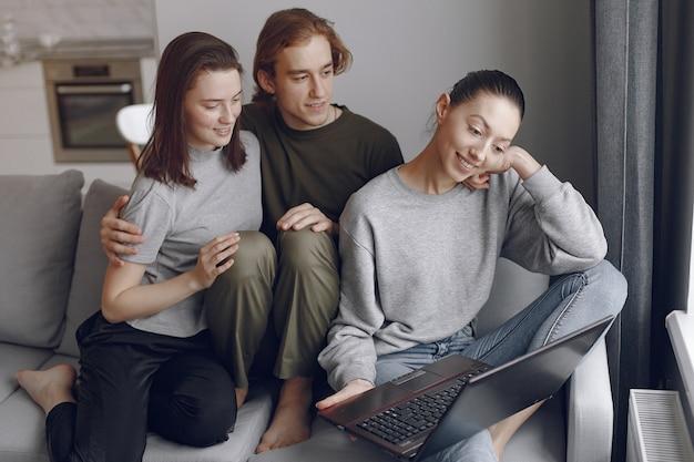 Amigos sentados en una cama en una habitación y usan una computadora portátil