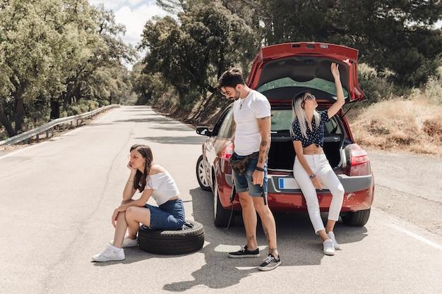Amigos sentados cerca del auto averiado en la carretera