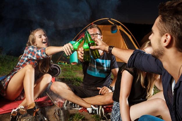 Amigos sentados cerca de la hoguera, bebiendo oso, sonriendo, hablando, descansando