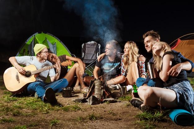 Amigos sentados cerca de la hoguera, sonriendo, abrazándose, descansando, tocando la guitarra