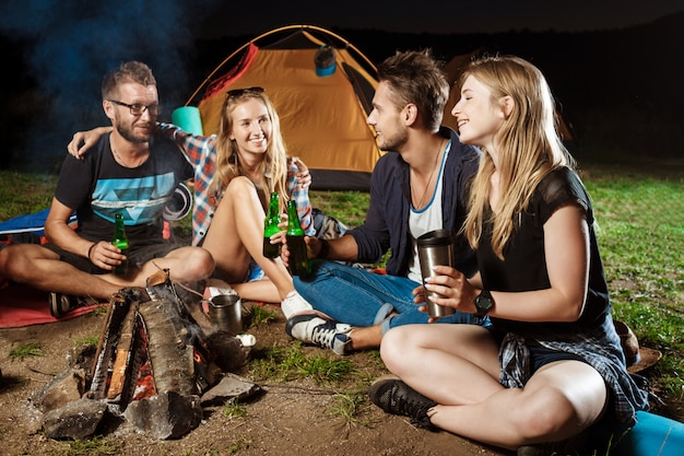 Amigos sentados cerca de la hoguera, sonriendo, hablando, descansando, bebiendo oso