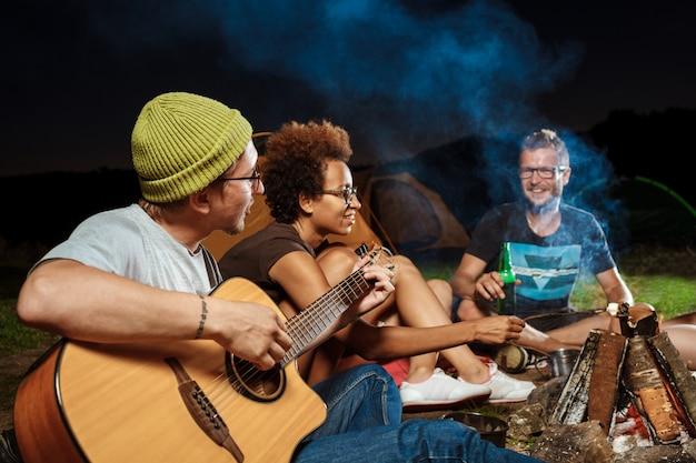 Amigos sentados cerca de la hoguera, sonriendo, hablando, descansando, tocando la guitarra
