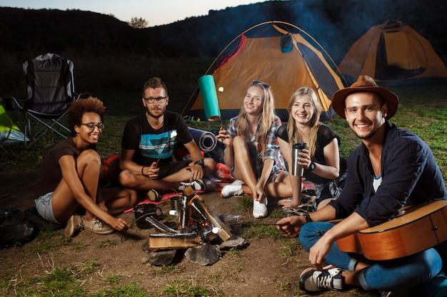 Amigos sentados cerca de la hoguera, sonriendo, tocando la guitarra camping grill malvavisco.